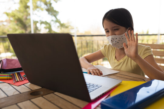 Girl wearing face mask having a video chat on laptop at home