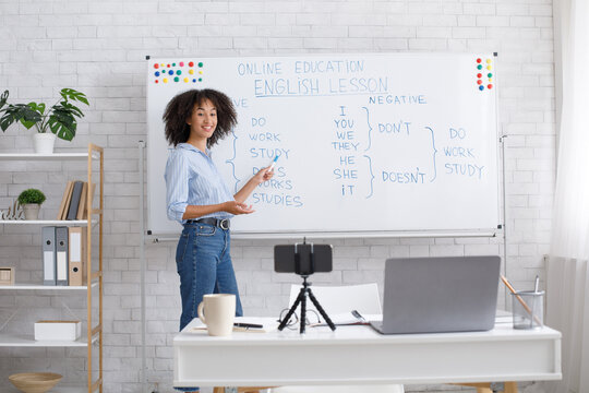 Smiling african american teacher points to white board with rules and records video for students in living room interior with laptop and smartphone