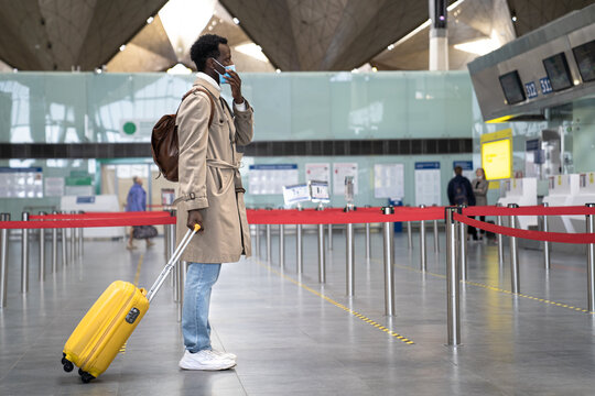 Black man with suitcase wearing face protective mask during virus epidemic, covid-19 pandemic while standing at almost empty airport terminal. Second wave coronavirus, new normal concept