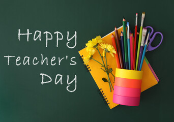 Text Happy Teacher's Day and stationery with flowers on green chalkboard, top view