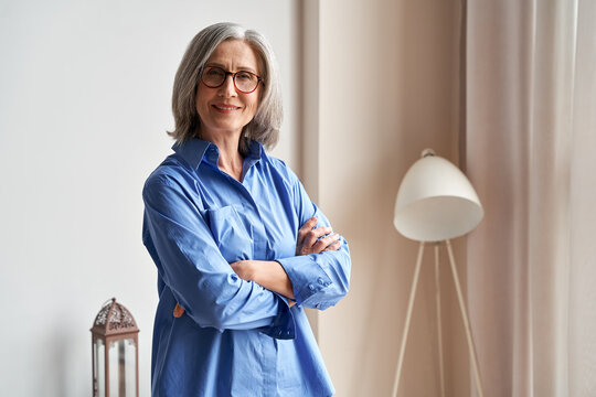 Smiling confident mature older woman standing arms crossed indoors looking at camera. Stylish classy middle aged senior 60s grey-haired lady wearing blue elegant shirt and glasses indoors, portrait.