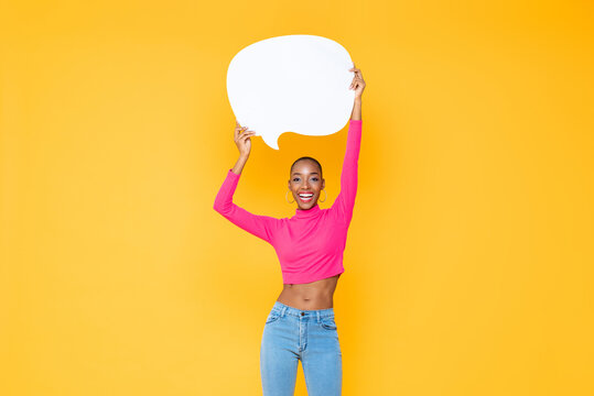 Smiling beautiful African American woman raising empty speech bubble isolated on colorful studio yellow background
