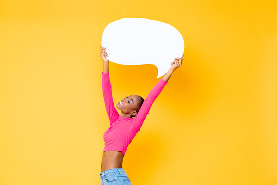 Smiling happy African American woman raising empty speech bubble isolated on colorful studio yellow background