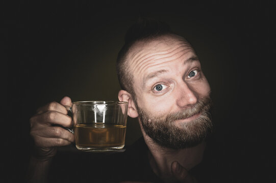 A friendly guy smiles at the camera and offers tea.