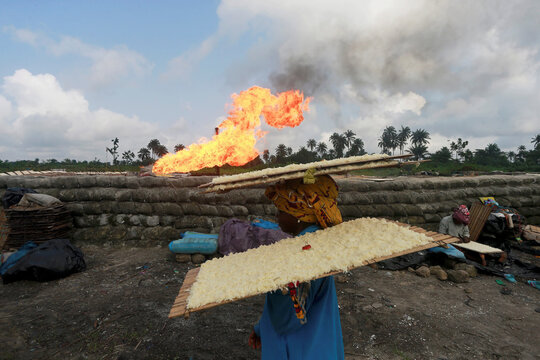 A woman carries wooden trays laid with tapioca at a flow station in Ughelli, Delta State