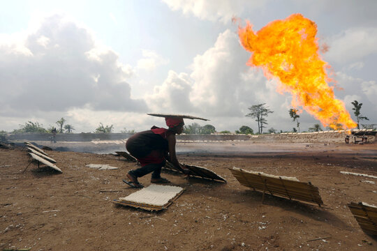 A woman scouts to set a wooden tray of cassava paste close to a gas flaring furnace in Ughelli, Delta State