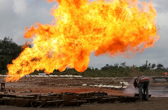 A man sets a wooden tray of tapioca on the ground close to a gas flaring furnace at a flow station in Ughelli, Delta State