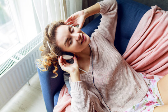 Wonderful woman with curly short hairs listen favorite music and lying  with closed eyes with pleasure. Wearing  cute pink  loungewear.