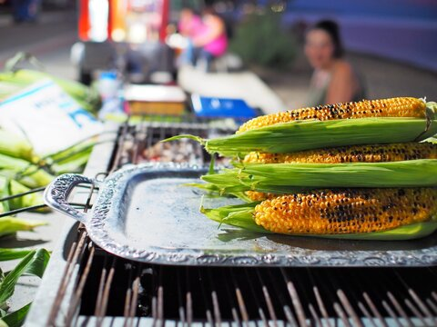 grilled fresh corns on a silver plate to keep them warm on the charcoals (street food)