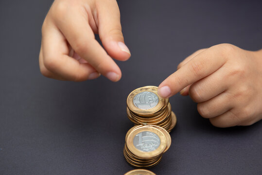 Child hands putting golden and silver coin on pile of coins. Concept of saving and spending money. Future investment. Long-term economic planning. Selective focus. Copy space.