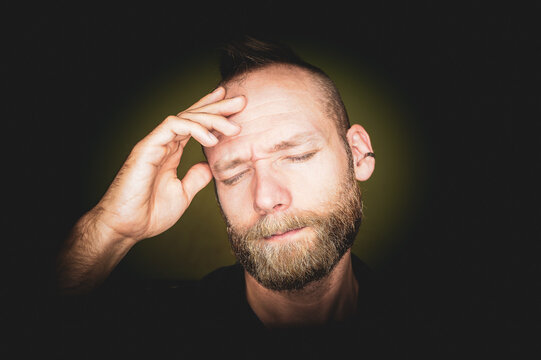 A middle-aged man with a headache is holding his head and eyes closed.