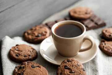 Coffee cup with cookies and chocolate on wooden table background. Mug of black coffee with...