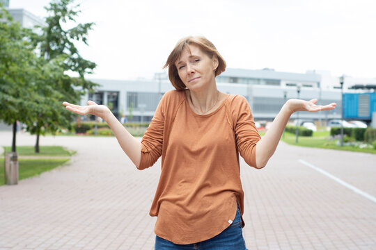 An adult redhead woman in casual clothes stands in the street spreading her arms and shrugging her shoulders in a questioning gesture. She does not know what is happening and what will happen next