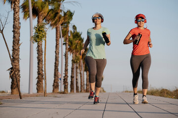 A shallow focus of two young females in sportswear with headphones jogging in a park