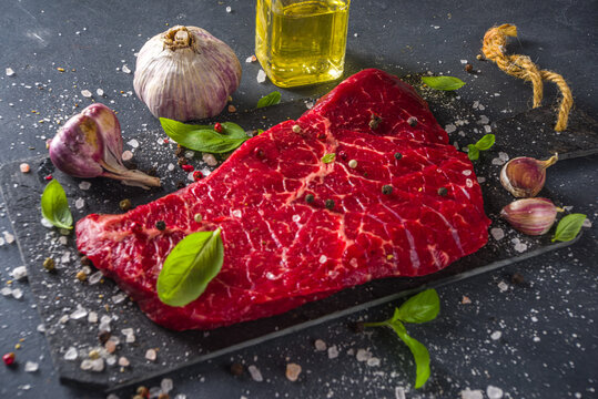 Raw meat beef steak on black background, with herbs and spices, top view.