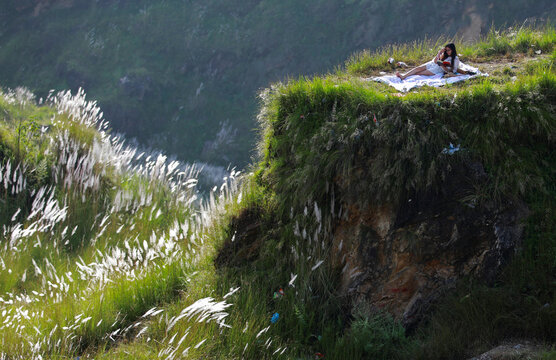 A woman reads a book at Chobhar a picnic spot in Kathmandu