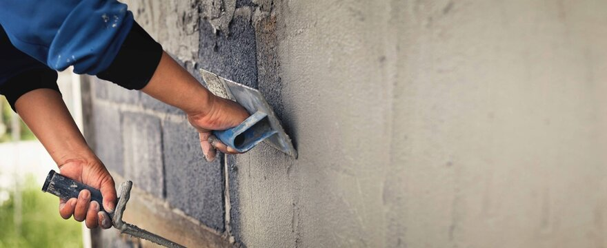 Concrete plasterers to create industrial workers background walls with plastering tools.