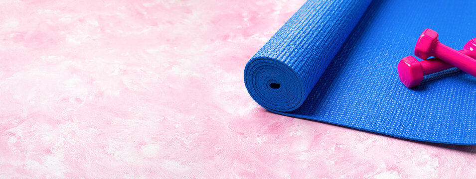 Blue yoga mat and dumbbells on pink background. Equipment for yoga, sport, fitness, workout. Concept healthy lifestyle, sport life, wellness. Long format with copy space