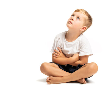 Litlle boy sitting on the floor and looking up on white background