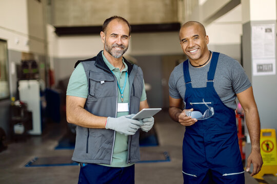 Happy auto mechanics working together in a workshop.