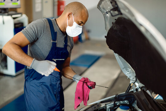 Black auto mechanic checking car oil while wearing face mask in repair shop.