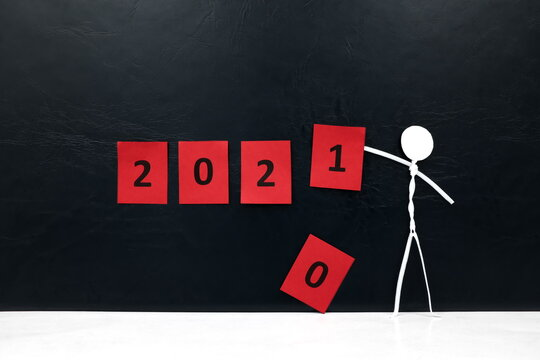 Stick man figure changing 2020 year red cubes to 2021 in black background with copy space. New Year celebration concept.