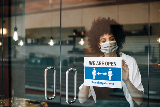 Coffee shop female owner with protective face mask, reopens after lockdown quarantine. Business woman hangs a open sign that asks to keep distance. New rules during Coronavirus pandemic