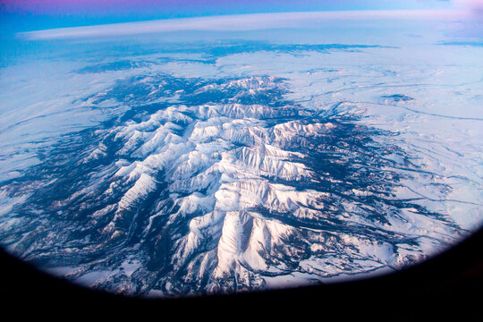 An aerial view of the Rocky Mountains about 100 miles west of Denver, Colorado.  Photo taken from a commercial airliner with curved shadow of the window visible.
