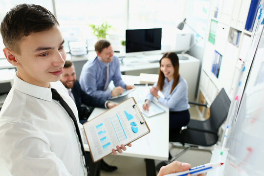Young handsome teacher man in suit with workgroup seminar board with chart coaching background. Lecturer for applicants retraining financial statistics management enterprise etiquette corporate spirit