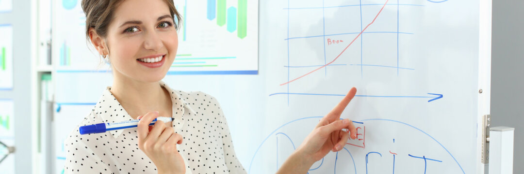 Portrait of smart lady pointing at important business charts and graphs on high-tech glass board. Attractive woman discussing higly increased corporation profit. Company meeting concept