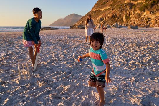 Portrait happy family playing cricket on sunny beach