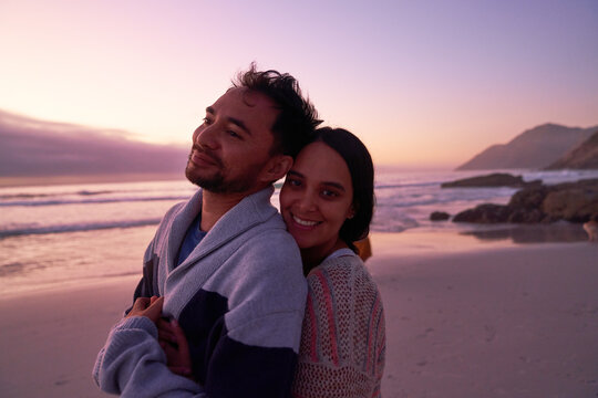 Portrait happy affectionate couple hugging on beach at sunset
