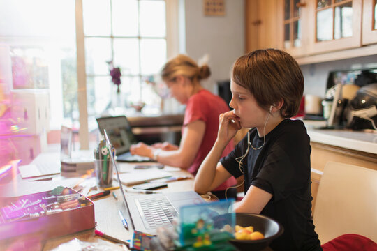 Focused boy homeschooling at laptop in kitchen