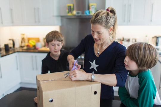 Mother and sons opening package in kitchen