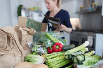 Woman unloading fresh produce from box in kitchen