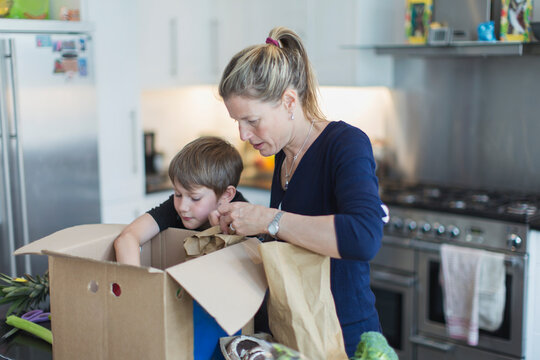 Mother and son unloading produce from box in kitchen