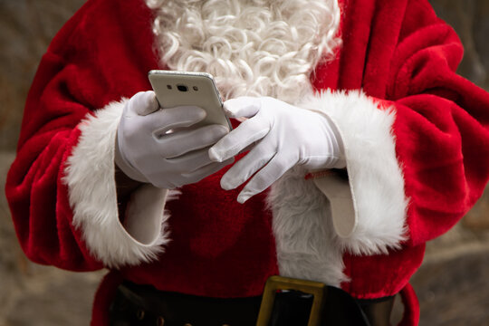 closeup of santa claus hands with mobile phone