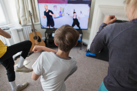 Mother and sons exercising online at TV in living room