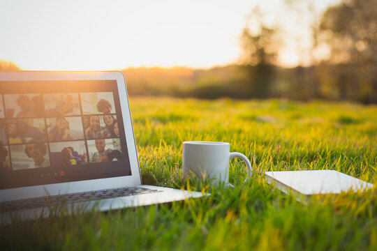Video chat on laptop screen next to coffee and book in sunny grass