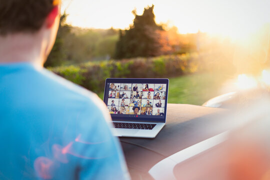 Man video chatting with friends on laptop screen on top of car