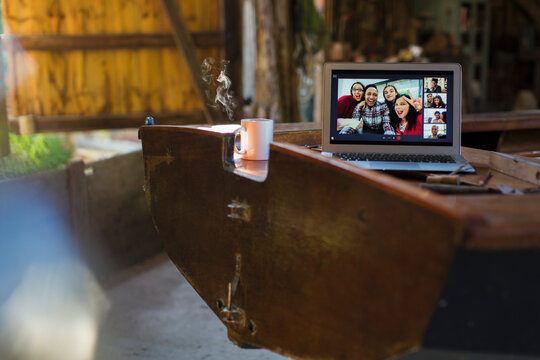 Friends video chatting on laptop screen on wooden boat