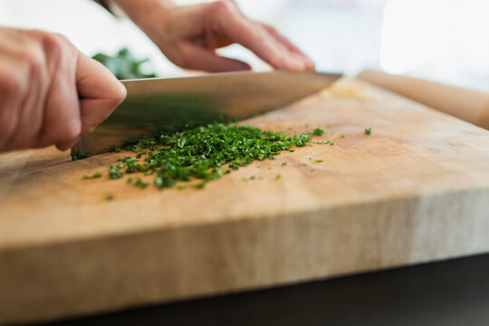 Close up woman cutting fresh herbs with knife on cutting board