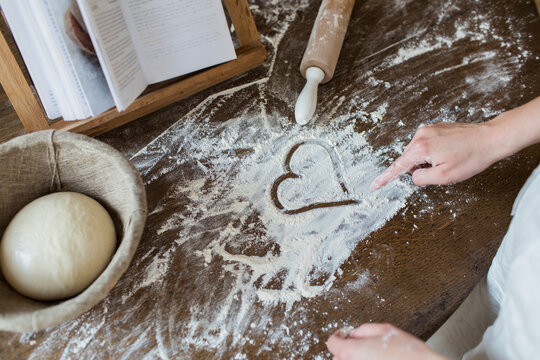 Teenage girl drawing heart shape in flour on kitchen counter
