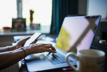 Close up woman working from home at laptop in home office
