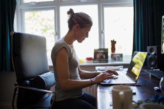 Woman working from home at laptop in home office