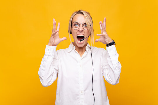 young woman telemarketer screaming with hands up in the air, feeling furious, frustrated, stressed and upset