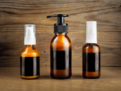Dark cosmetic amber glass bottles set with black blank labels for cosmetics on a wooden background.