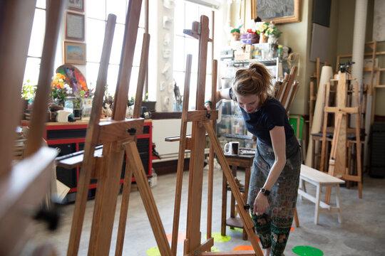 Female artist preparing easel in art studio