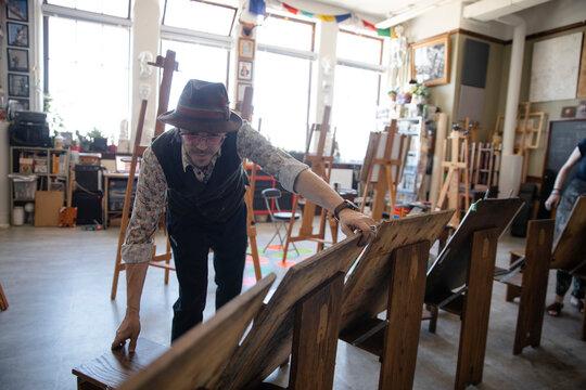 Male artist preparing easels for art class in studio