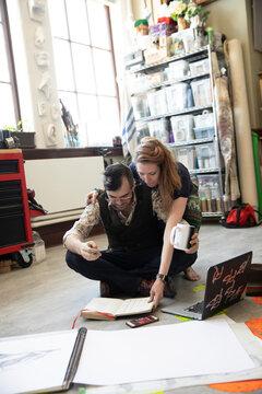 Artist couple planning on floor of art studio